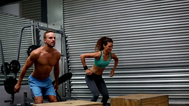 Fit couple doing set of box jumps video