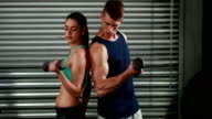 Fit couple exercising with dumbbells video