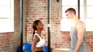 Fit couple high fiving in gym gym video