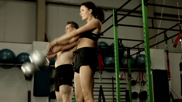 Fit couple squatting with kettlebells video