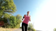 Fit female runner running on countryside road video
