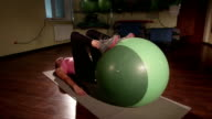 Fit girl exercising at fitness club with stability ball for core training video