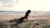 Fit girl stretching on surfboard at sunrise on the beach. Slide. Slow motion. video
