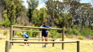 Fit man and woman climb a hurdles during obstacle course video