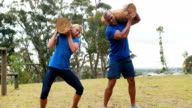 Fit man and woman lifting heavy wooden logs during obstacle course video