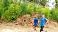 Fit man and woman to climb a wooden wall during obstacle course video
