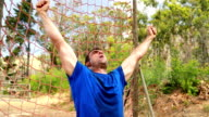 Fit man cheering during obstacle course video