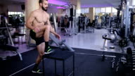 Fit man doing box jumps in gym video