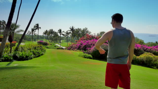 Fit Man Enjoying the View, Tropical Golf Course, Palm Trees and Grass video
