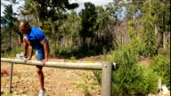Fit man jumping over the hurdles during obstacle course video