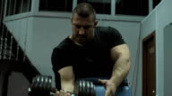 Fit man lifting dumbbell at gym video