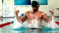 Fit man raising arms in the pool video