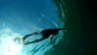 UNDERWATER LOW ANGLE: Fit man swimming above rocky coral seabed in emerald sea video