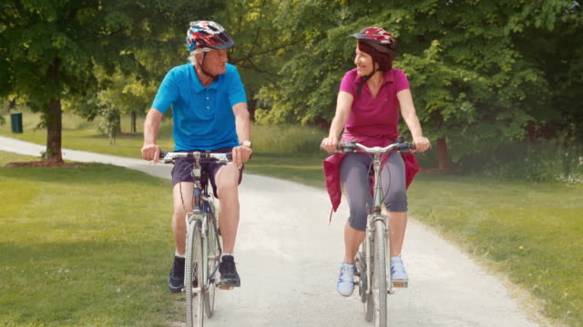TS Fit senior couple riding bikes through the park video