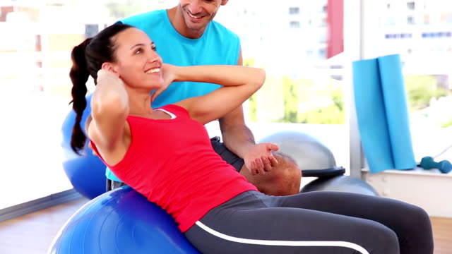 Fit woman doing sit ups on exercise ball with trainer video