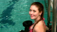 Fit woman holding weights in the pool and smiling at the camera video