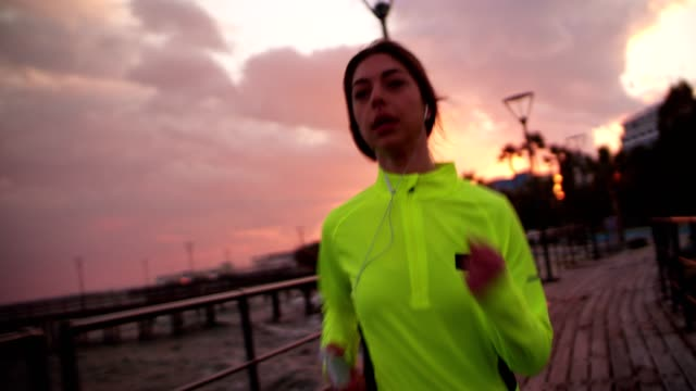 Fit woman jogging and listening to music on her smartphone video