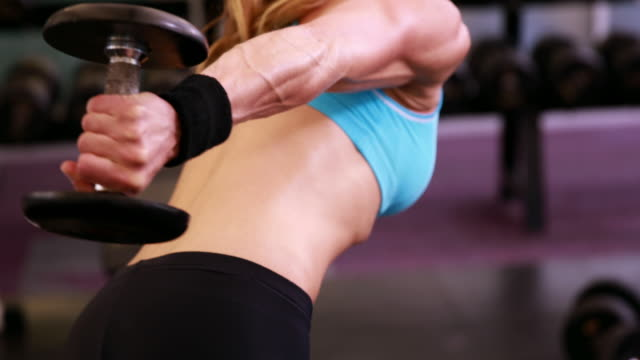 Fit woman lifting dumbbells at gym session video