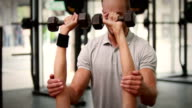 Fit woman lifting dumbbells with trainer video