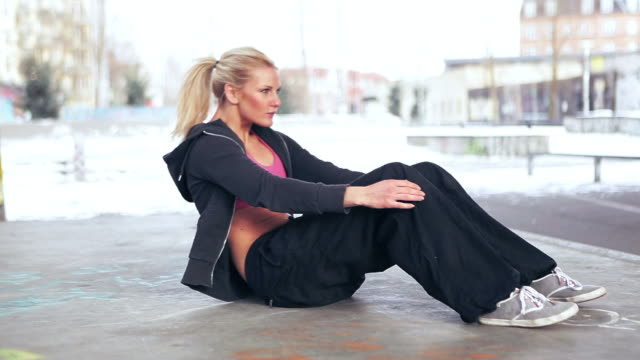 Fit woman performing sit-ups outdoor video