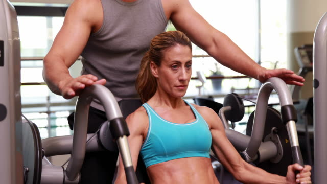Fit woman using weights machine for arms with her trainer video