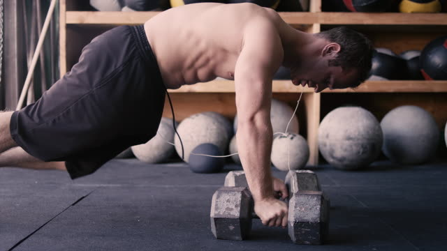 A fit young man doing push-ups with dumbbells in a gym video