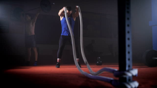 Fit young man holds rope in his hands and makes heavy rope training workout video