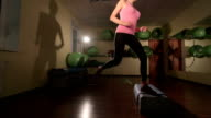 JIB CRANE: Fit young woman doing step aerobics exercise in fitness club video