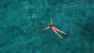 AERIAL: Fit young woman swimming in amazing ocean and watching surroundings video