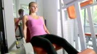 Fit young woman training in health fitness club using leg extension machine video