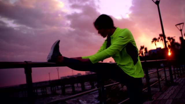 Fit young woman warming up her legs at sunset video