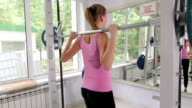Fit young woman working out in fitness club doing exercise with barbell video