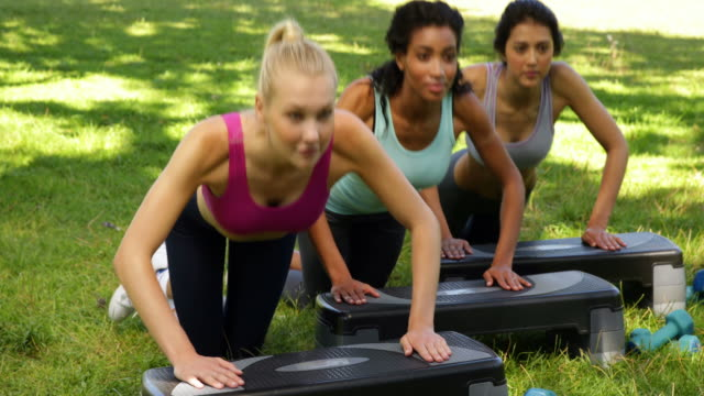 Fitness class doing press ups on steps together video