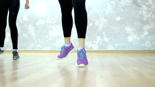 Fitness instructor exercising with a group video
