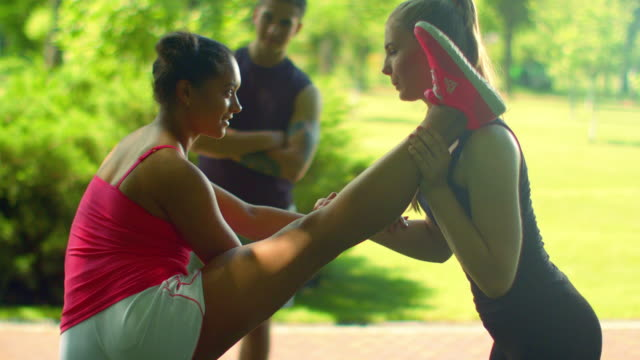 Fitness instructor helps to do stretching exercise. Multi ethnic friends video