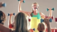Fitness instructor leading exercise class of women video
