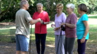 Fitness instructor talking with senior people in park video