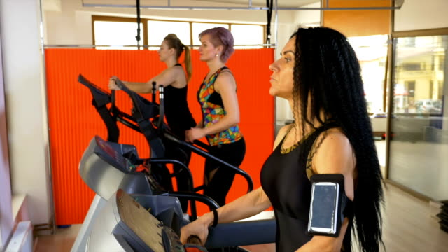 Fitness instructor training on the treadmill setting up smartphone tracking app video