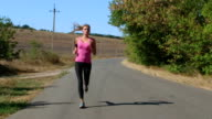 Fitness running woman jogging during outdoor workout along country road video
