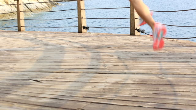 fitness sports woman legs running on wooden boardwalk seaside video