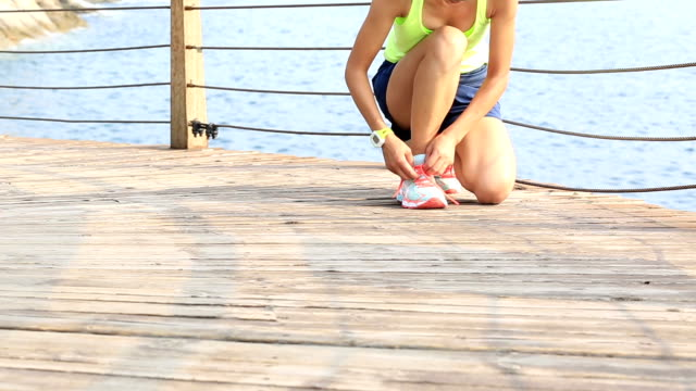 fitness sports woman running on wooden boardwalk seaside video