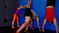 Fitness trainer assisting people to perform handstand video