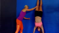 Fitness trainer assisting woman to perform handstand video