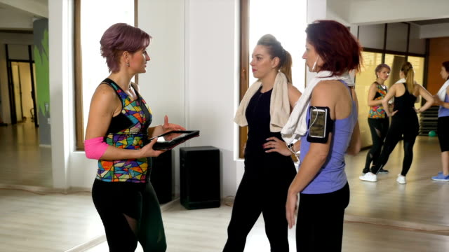 Fitness trainer at the gym showing workout schedule using a digital tablet pc computer to women video