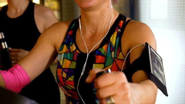 Fitness trainer with headphones and tracker gadget working out on the stepper video
