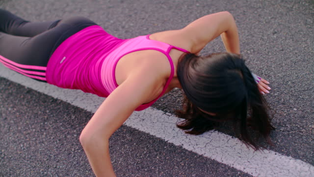 Fitness woman push ups on city road. Female athlete doing push up exercise video