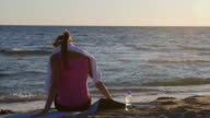 Fitness woman relaxing after workout on beach video