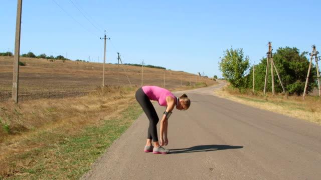 Fitness woman runner lacing sport footwear before jogging outdoor video