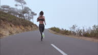 Fitness woman sprinting on countryside highway video