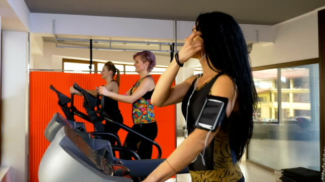 Fitness woman with smartphone arm strap listening to music and doing sport activity on the treadmill video